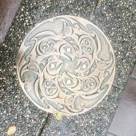 Decorative medallion in sidewalk.
